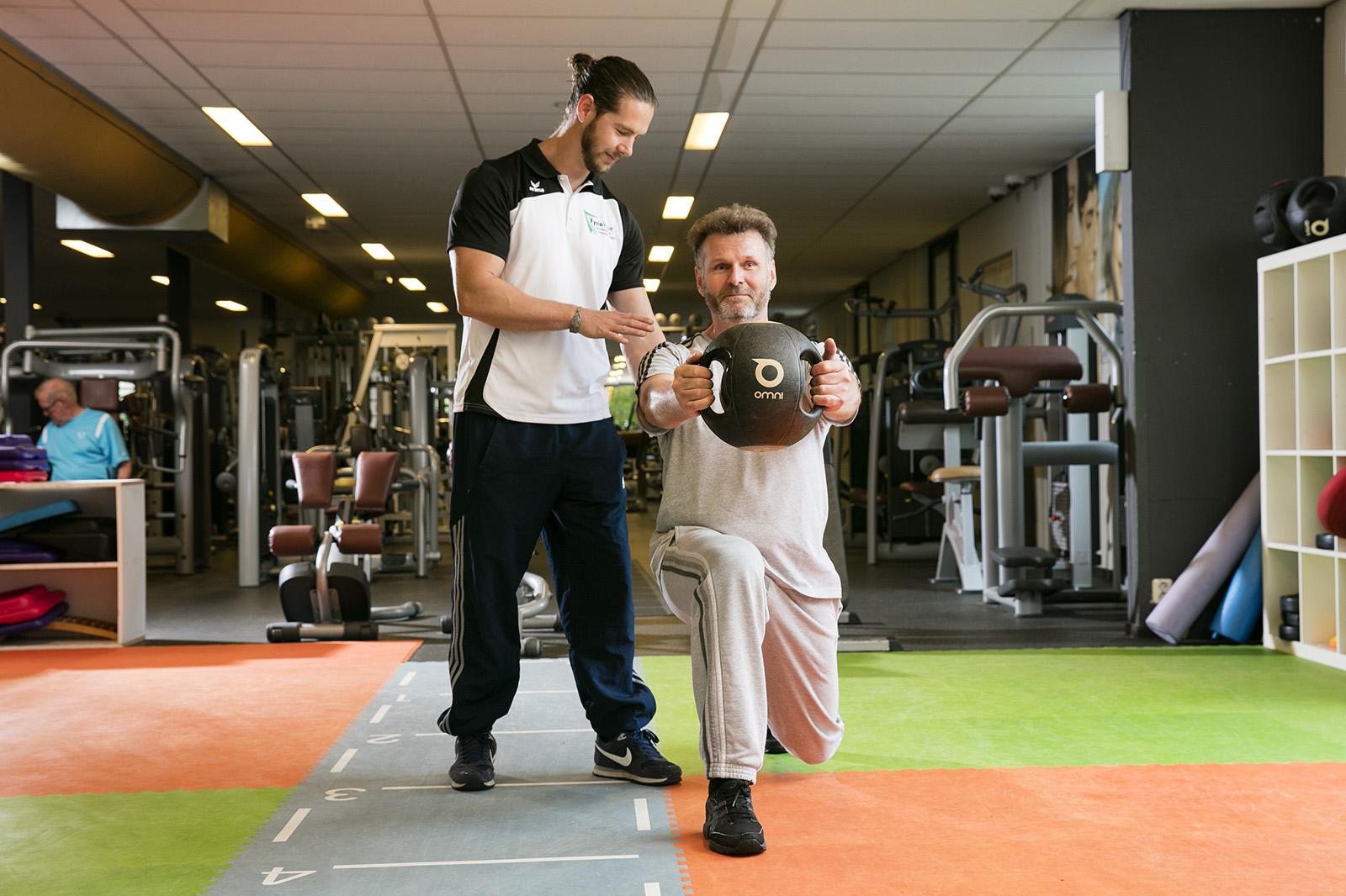 Foto van Michel Sleijpen met patient in behandelzaal met trainingsbal